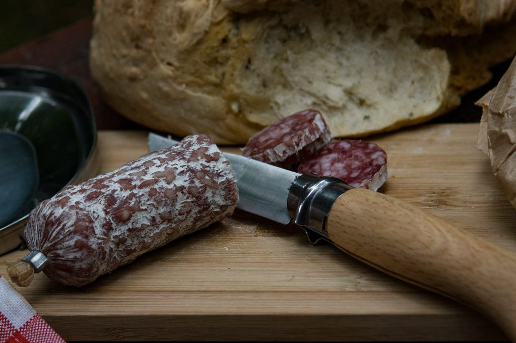 Opinel knife cutting sausage